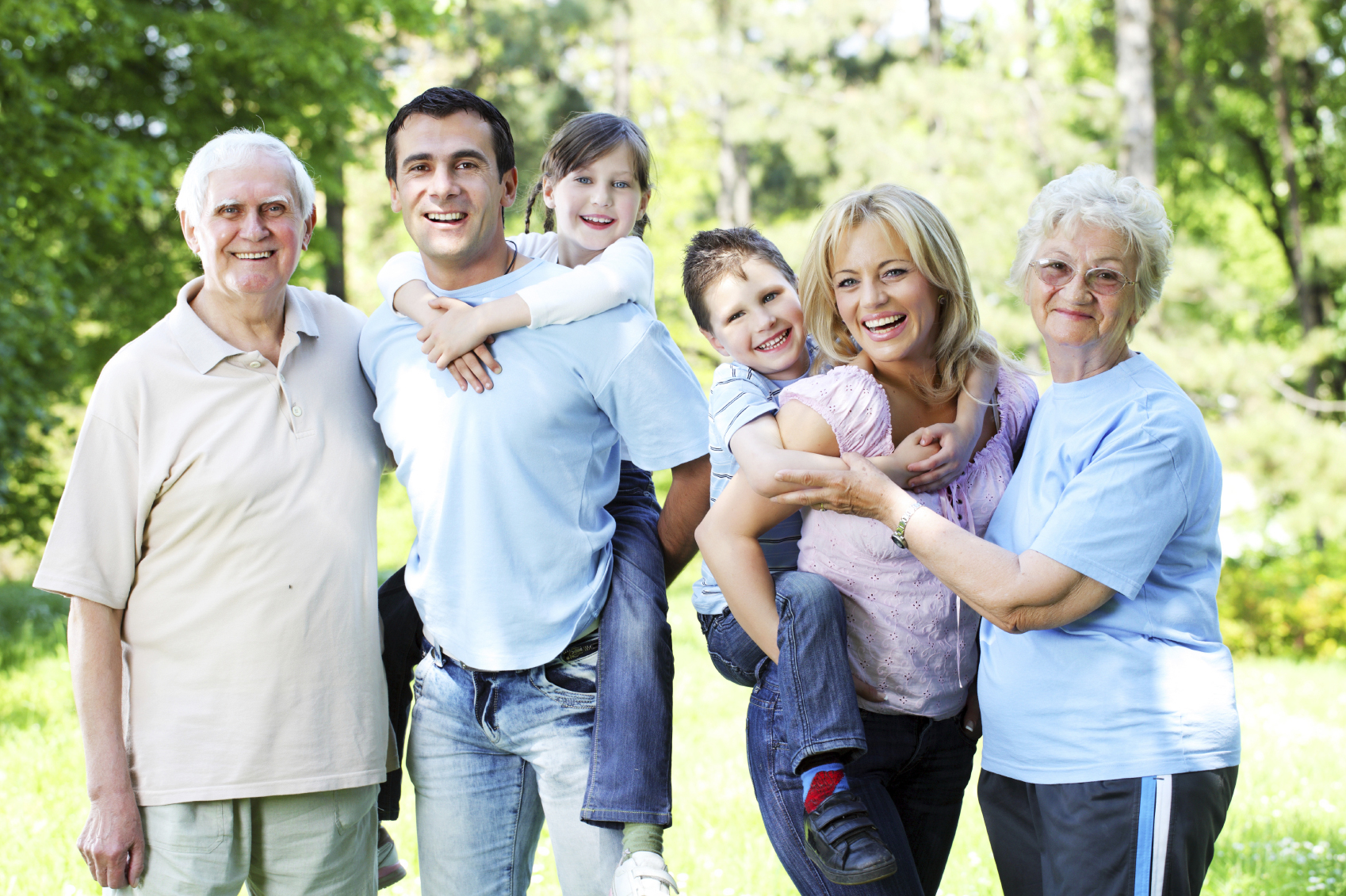Extended happy family standing in the park. – Renewed ...